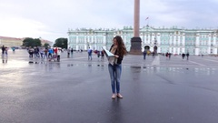 Woman look to city map on Palace Square, fast orbiting shot Stock Footage