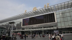 WS Shanghai Railway Station with big screen and people walking in foreground / Stock Footage