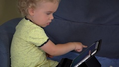 Curious blond kid touching tablet computer screen sitting on couch Stock Footage