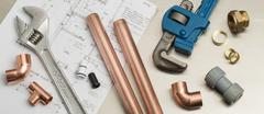 Plumbers Tools and Plumbing Materials Banner on House Plans Stock Photos
