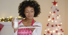 Happy young woman with milk and cookies for Santa Stock Footage