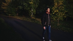 Young calm man in black jacket walking in the autumn park dramatic light Stock Footage