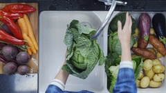 Woman's hands washing kale leaves under running water Stock Footage