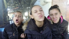 Happy kids making faces grimace at first gondola cable car ride Stock Footage