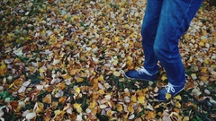 Man legs in the jeans boots walking on the autumn leaves in the park slow motion Stock Footage