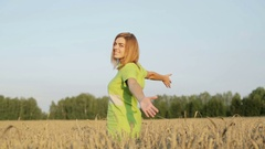 Happy girl with outstretched arms  in a wheat field. Stock Footage