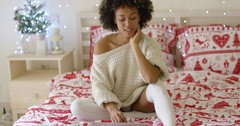 Woman in oversized sweater on bed using laptop Stock Footage