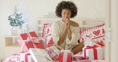 Excited young woman with a bed full of Xmas gifts Stock Footage