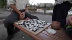 MS TU TD Men playing traditional board game on park bench / Beijing, China Stock Footage