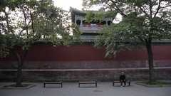 MS TU Elderly woman sitting in front of red wall / Beijing, China Stock Footage