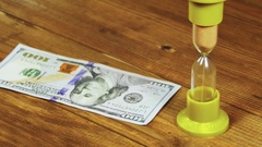 Dollar Banknotes Falling on a Wooden Table and Hourglass Stock Footage