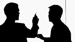 MS Silhouette of two businessmen talking and pointing to white board / China Stock Footage