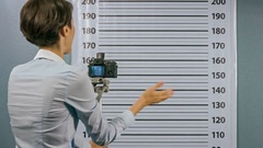 Police woman takes a picture on the camera man who is handcuffed. Mugshot. Stock Footage