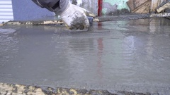Worker using trowel and leveling fresh concreted rocks of building Stock Footage