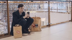 Disappointed young man sitting on the floor in mall without money after Black Stock Footage