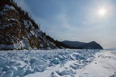 Sun over clumps of blue ice on the snow. Beautiful winter landscape in Lake Stock Photos