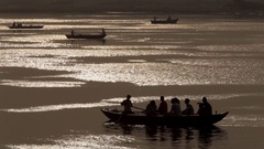 WS Silhouettes of boats rowing across Ganges river at sunset / India Stock Footage