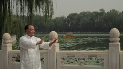 MS Mature man doing Tai Chi by lake / Beijing, China Stock Footage
