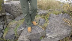 Male legs in yellow boots go on  track in hill and rocks.  Stock Footage