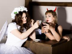 Portrait of angel and devil womans drink coffee nad wine Stock Photos