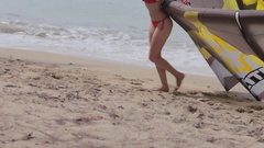 WS TU Young blonde woman dragging surf kite up beach / Singapore Stock Footage