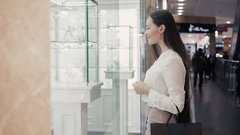 Beautiful young woman looking in a shop window with watches and luxury juwellery Stock Footage