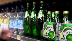 Woman buying Perrier carbonated natural spring water inside Walmart store Stock Footage