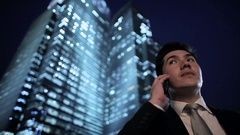 MH LA LD Young Businessman Talking on Phone in Evening with Illuminated Stock Footage