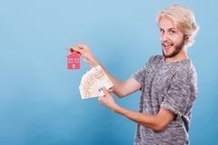 Man holding money and keys to house Stock Photos