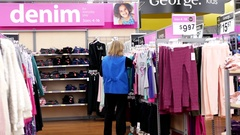 Worker checking price tag for display clothes on sale inside Walmart store Stock Footage