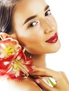 Young pretty brunette woman with red flower amaryllis close up i Stock Photos