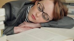 CU LD Young Woman Resting on Books with Eyes Closed Stock Footage