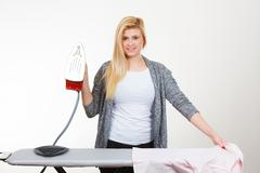 Happy woman ironing creased clothes Kuvituskuvat
