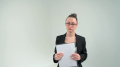 Young woman in formalwear adjusting her eyeglasses and looking at camera Stock Footage