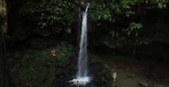 Wide aerial pulling back on Emerald Pool waterfall in Dominica Stock Footage
