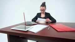 Businesswomanworking at her office desk with documents and laptop. Stock Footage