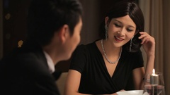MS Elegantly dressed couple talking during candle lit dinner / China Stock Footage