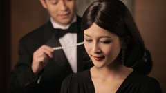CU Man in tuxedo putting diamond necklace on young women's neck / China Stock Footage