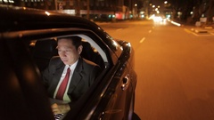 MH TS POV Businessman Riding in Back Seat of Car Working on Laptop at Night / Stock Footage