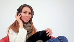 Young woman  wearing headphones and holding a purple LP microgroove vinyl record Stock Footage