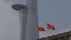 MH LA LD Vietnam and Communist Flags Waving in front of Bitexco Financial Tower Stock Footage