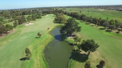 Backward flight over Patterson River Golf Club passing playing golfers Stock Footage