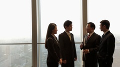 MS Senior businessman talking to young business people in office / Beijing, Arkistovideo