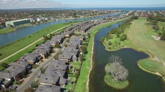 Backward flight above Bonbeach suburb houses and Patterson River Stock Footage