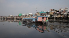 BOAT POV WS PAN Boat Floating Along River with Houses Along Bank / Hoi An, Stock Footage