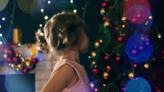 Toddler girl, background of decorated Christmas tree, blurred garlands light Stock Footage