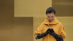 MS Young woman in yellow coat talking on mobile phone / China Stock Footage