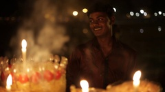 MS Candles burning in foreground, young man smiling in background / New Delhi, Stock Footage