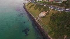 Forward flight along coastal highway with camera tilt revealing horizon Stock Footage