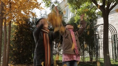 MS Boy and girl jumping and throwing dry leaves in park / China Stock Footage